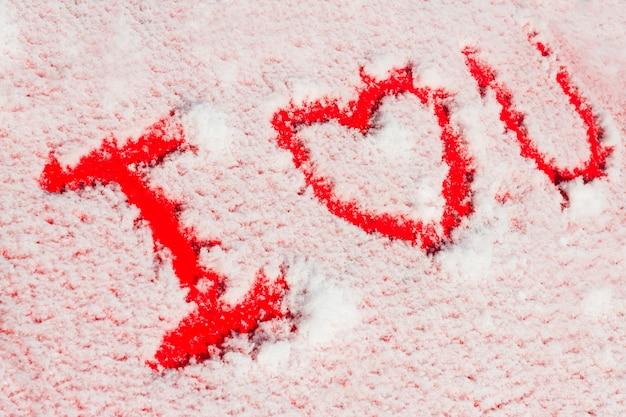 Parole che ti amo sulla macchina rossa innevata. concetto romantico per san valentino