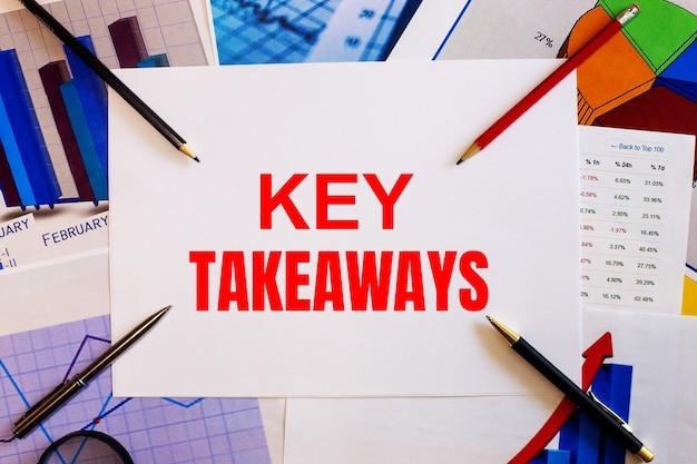 Le parole key takeaways sono scritte su uno sfondo bianco vicino a grafici, penne e matite colorate. concetto di affari