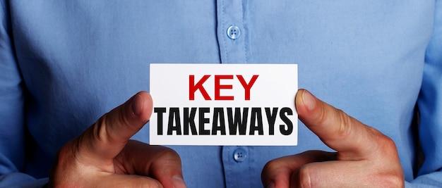 Le parole key takeaways sono scritte su un biglietto da visita bianco nelle mani di un uomo. concetto di affari