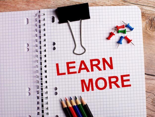 Le parole per saperne di più sono scritte in un taccuino vicino a matite e bottoni multicolori su una superficie di legno