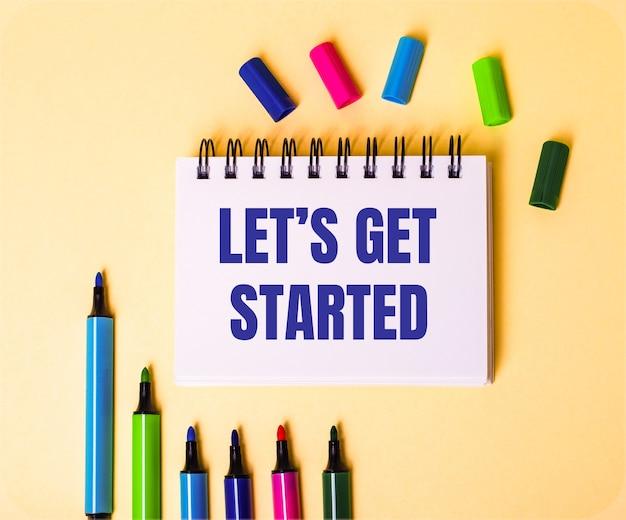 Le parole let is get started scritte in un taccuino bianco su uno sfondo beige vicino a pennarelli multicolori