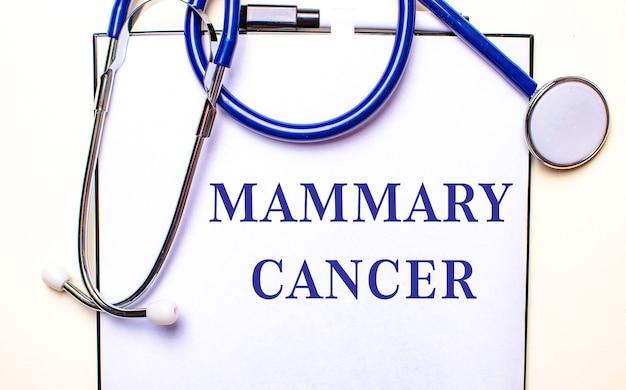 Le parole cancro alla mammaria sono scritte su un foglio bianco vicino allo stetoscopio