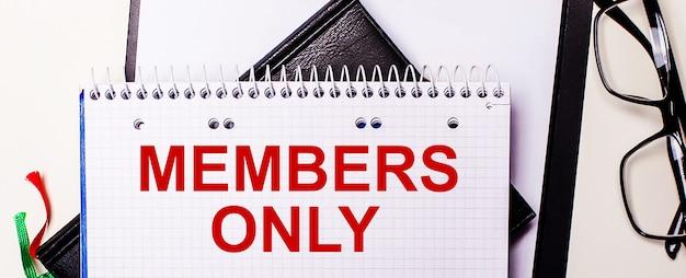 Le parole solo membri sono scritte in rosso su un taccuino bianco accanto agli occhiali con la montatura nera.