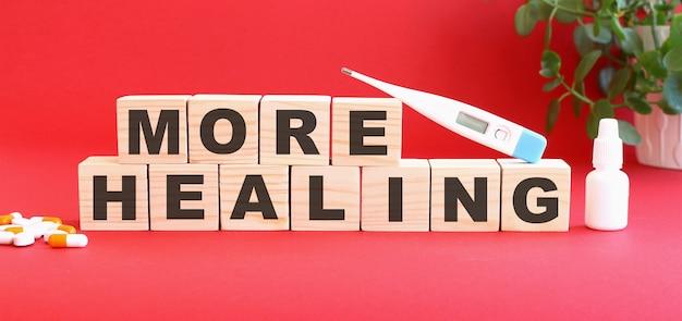 La scritta more healing è composta da cubi di legno su sfondo rosso con farmaci.