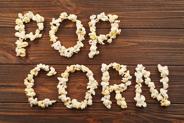 Parole pop corn a base di chicchi di mais su una superficie di legno