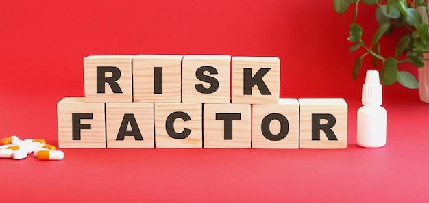 La scritta fattore di rischio è composta da cubi di legno su sfondo rosso. concetto medico.