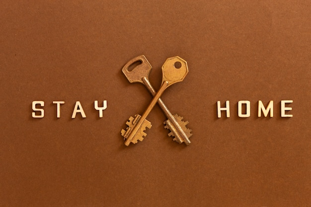 Le parole restano a casa fatte con lettere di legno e due chiavi, concetto di auto quarantena a casa come misura preventiva contro lo scoppio del virus corona covid 19.