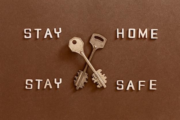 Words stay home stai al sicuro con lettere di legno e due chiavi, concetto di auto quarantena a casa come misura preventiva contro lo scoppio del virus corona covid 19.