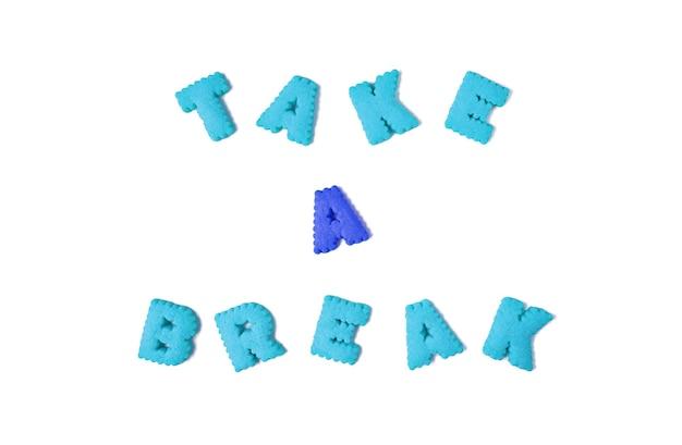 Le parole prendi una pausa scritte con biscotti a forma di alfabeto rosso e blu su fondo bianco
