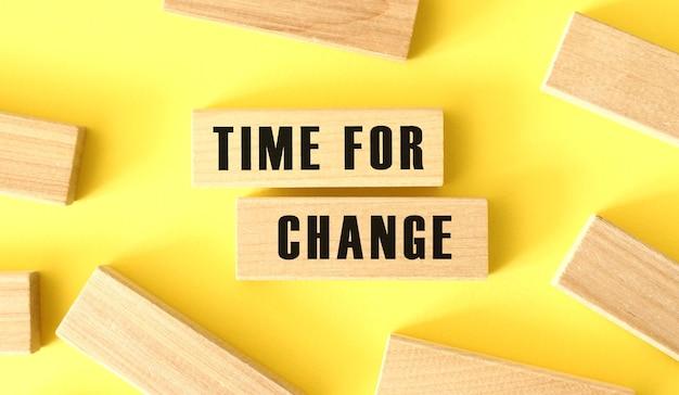Le parole time for change sono scritte su blocchi di legno su sfondo giallo.