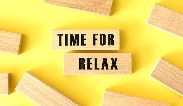 Le parole time for relax sono scritte su blocchi di legno su sfondo giallo. concetto di affari