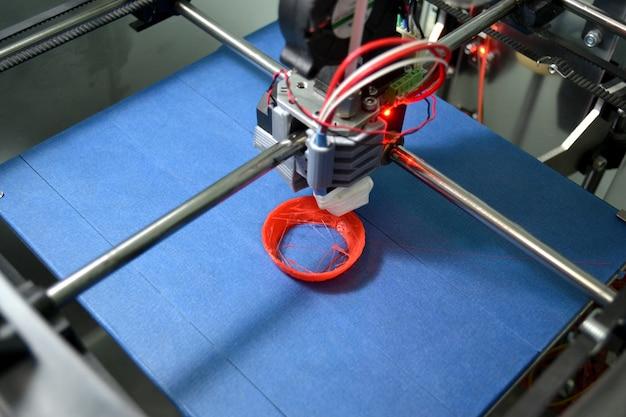 Chiudere la stampante 3d del lavoro. stampa stampante 3d oggetto plastica arancione su sfondo blu. filamento di filo di plastica, moderna tecnologia di stampa. tecnologia additiva progressiva