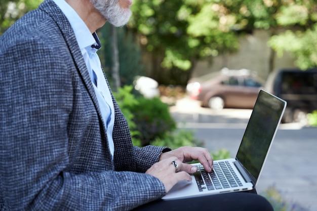 Lavora ovunque un uomo d'affari maturo che lavora al laptop mentre è seduto all'aperto durante il giorno