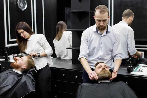 Lavora in un barbiere. due maestri al lavoro.