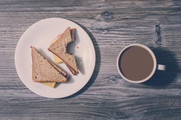 Al lavoro. panino al formaggio pungente con briciole su un piatto bianco, tazza di caffè su fondo di legno. vista dall'alto, effetto vintage.