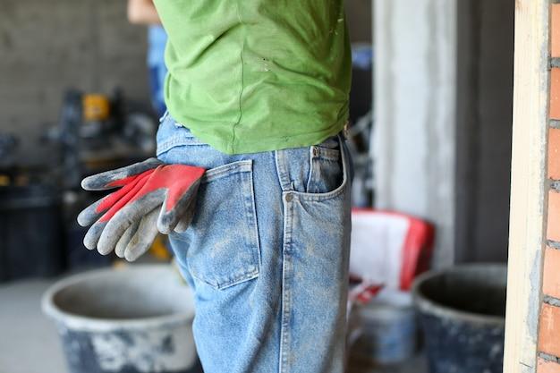 Abiti da lavoro su costruttore, guanti di gomma in tasca. i guanti eliminano il rischio di danni alle mani della pelle in condizioni di costruzione pericolose. comfort e affidabilità uniformi di alto livello