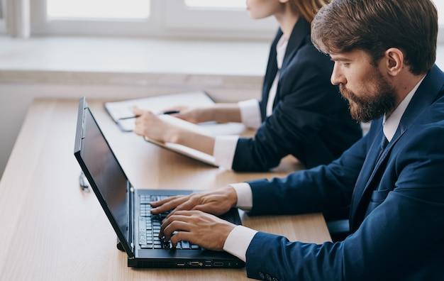 Colleghi di lavoro in giacca e cravatta che lavorano team di manager ufficio portatile scrivania