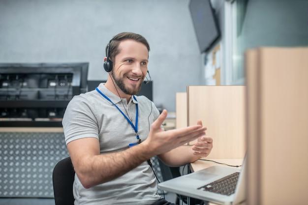 Lavoro, emozione. giovane adulto sorridente gesticolando uomo in cuffie vicino al computer portatile al posto di lavoro in camera