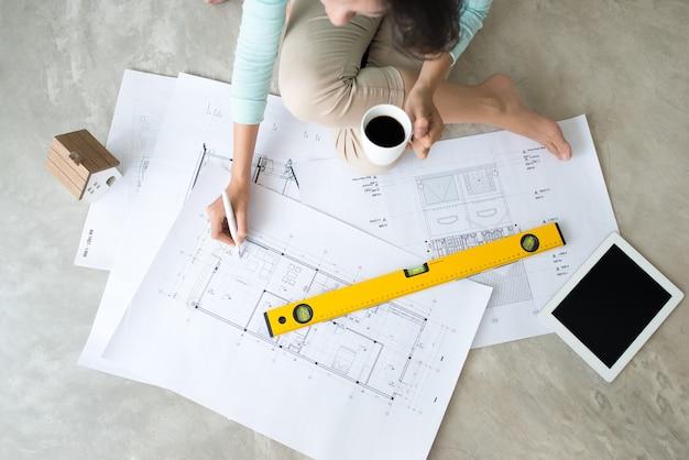 Lavora ovunque. fiduciosa giovane bella donna asiatica che lavora con il progetto mentre è seduta sul pavimento a casa