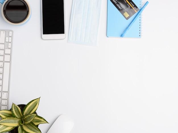 Lavora da casa concetto portatile, taccuino, maschera, caffè, carta di credito sul muro bianco, piatto laici