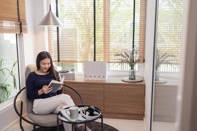 Concetto di lavoro da casa una bella donna seduta su una sedia moderna in una stanza minimale ben arredata che legge un libro famoso.