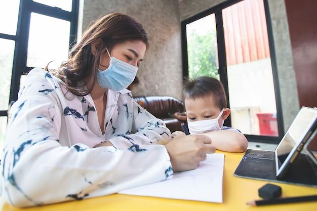 Lavoro da casa. madre insegna e gioca con suo figlio mentre mette in quarantena per coronavirus covid-19. madre e figlio che indossano una maschera protettiva mentre lavorano a casa durante l'epidemia di coronavirus.