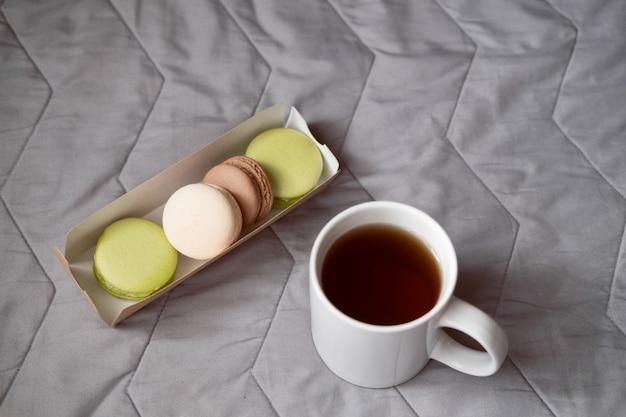 Lavoro da casa. guardando un film con tè e torta. macarons con una tazza di tè. fine settimana pigro.