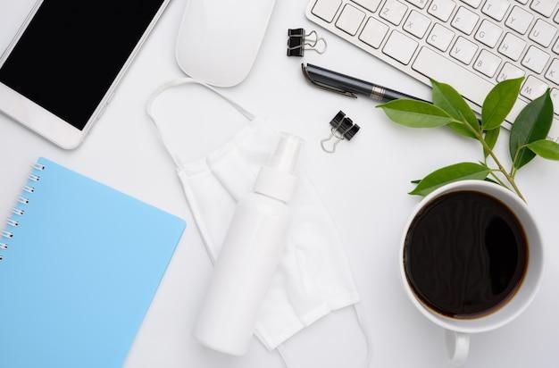 Lavora da casa con laptop, maschera di stoffa, tazza di caffè, penna, telefono sul muro bianco, piatto disteso