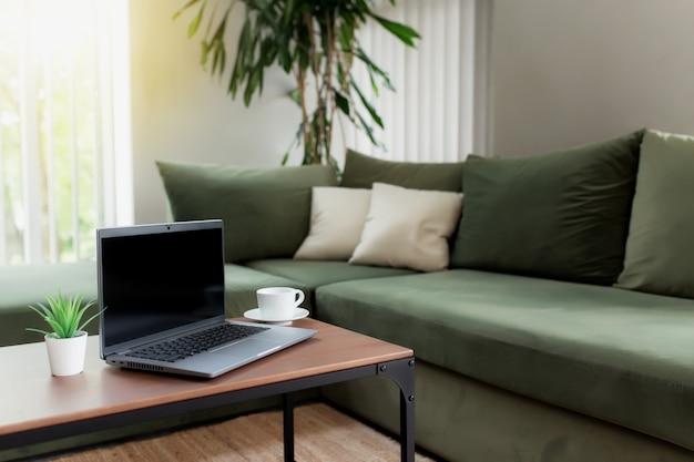 Lavoro da casa, spazio di lavoro, desktop, concetto di lavoro remoto, notebook grigio, schermo vuoto nero su tavolo di legno con tazza di caffè bianca, divano verde, vaso di fiori. appartamenti eleganti soggiorno