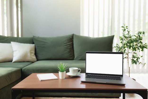 Lavoro da casa, spazio di lavoro, desktop, concetto di lavoro a distanza, computer portatile sottile grigio su tavolo di legno marrone con tazza di caffè bianca, divano verde, vaso di fiori, blocco note. appartamenti eleganti zona comfort