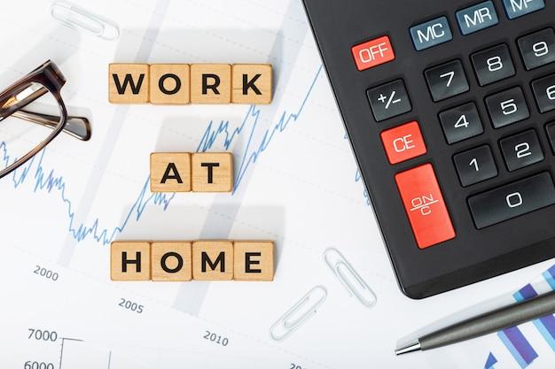 Concetto di lavoro a casa. blocchi di legno con frase, calcolatrice e grafici stampati. sfondo di affari