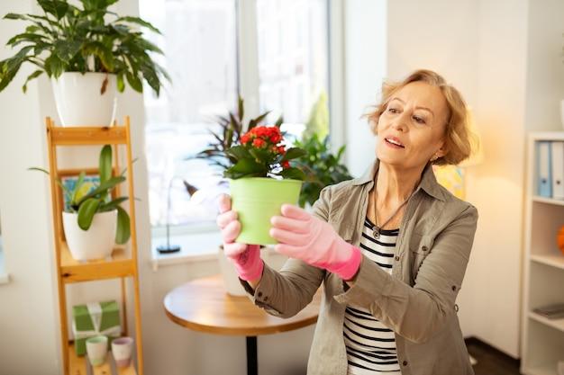 Il lavoro è fatto. gioiosa e piacevole donna che indossa i guanti mentre tiene in mano un vaso di fiori