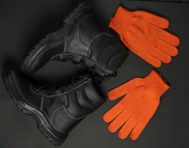 Scarpe e guanti di cuoio del lavoro su fondo nero. equipaggiamento di sicurezza. vista dall'alto