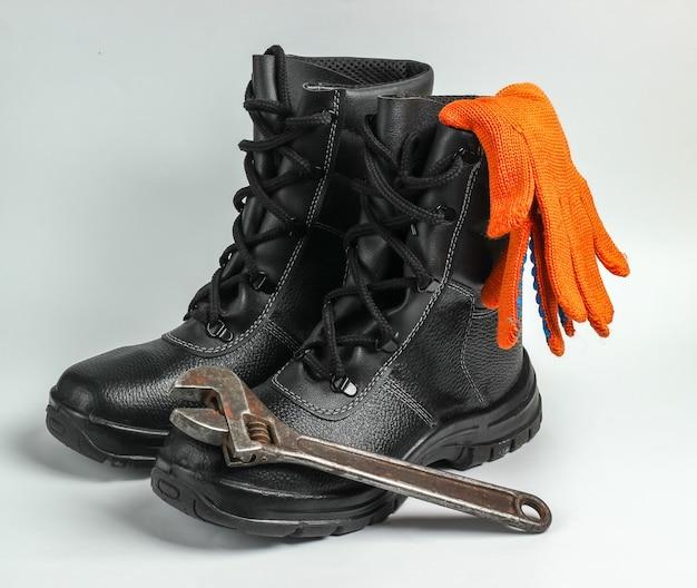 Scarpe da lavoro in pelle, guanti, chiave inglese su sfondo bianco. attrezzatura di sicurezza e strumento industriale.
