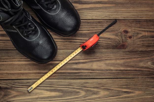Scarpe di cuoio da lavoro e metro a nastro. strumenti e strumenti di lavoro industriali, equipaggiamenti di sicurezza su fondo di legno. vista dall'alto