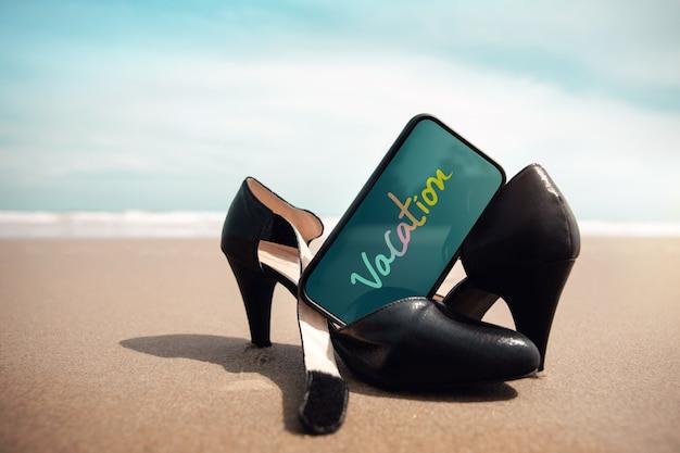 Concetto di equilibrio tra lavoro e vita privata. la donna d'affari si toglie le scarpe da lavoro e le lascia sulla spiaggia di sabbia per camminare nel mare. messaggio di vacanza sul cellulare. vacanze estive. inquadratura dal basso