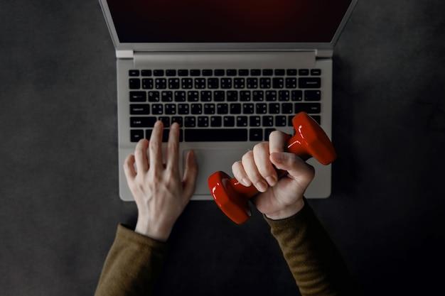 Concetto di equilibrio tra lavoro e vita familiare. giovane donna che tiene un manubrio per esercitare la mano e il braccio mentre si lavora sul computer portatile