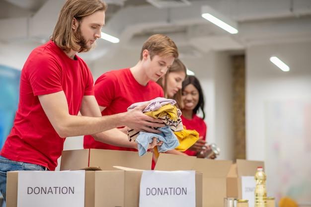 Atmosfera lavorativa. ragazzi e ragazze seri coinvolti si offrono volontari piegando con cura i vestiti delle donazioni in scatole di cartone