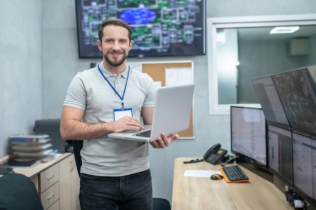 Lavoro, osservazione. sorridente giovane uomo barbuto con il computer portatile in mano in una sala high-tech appositamente attrezzata
