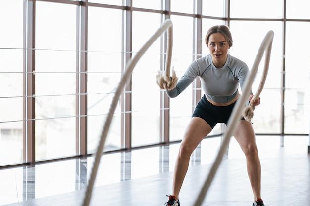 Allenati in un club vicino alle finestre. la giovane donna allegra ha una giornata di fitness in palestra al mattino