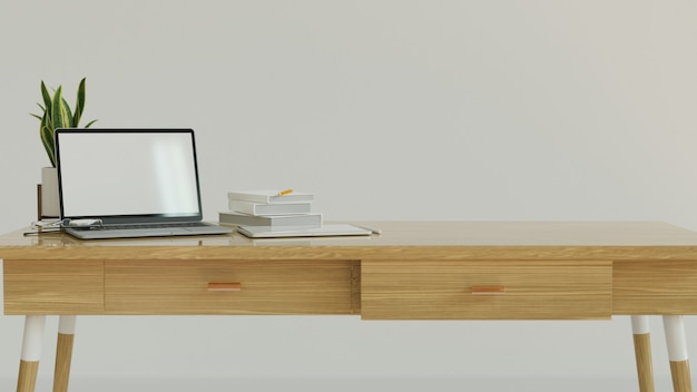 Spazio di lavoro progettato con tavolo in legno a parete bianca e laptop mock up con schermo vuoto e spazio copia