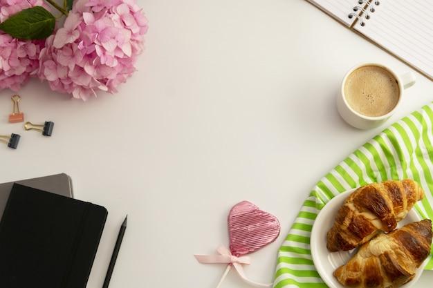 Cornice dello spazio di lavoro con tazza di caffè, croissant, ortensie rosa e quaderni.