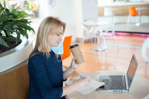 Lavora e studia durante una pandemia. distanza sociale. la bionda femmina si siede al tavolo di un caffè vuoto nel centro commerciale con una tazza