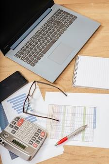 Tavolo da lavoro a casa con penna, documenti, bollette, grafici, bicchieri, computer e calcolatrice. concetto di lavoro a casa, conti correnti, economia della casa. vista aerea.