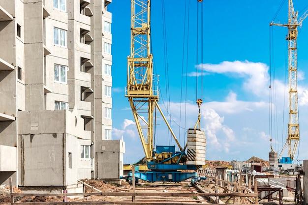 Il lavoro di una gru a torre durante la costruzione di una casa a pannelli in cemento armato