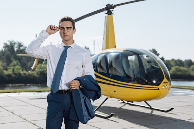 Visita di lavoro. affascinante giovane uomo d'affari che visita una pista per elicotteri e si aggiusta gli occhiali mentre controlla il luogo