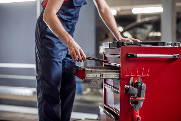 Lavoro, officina. mani maschii con strumento di lavoro vicino alla scatola con parti in officina, il viso non è visibile