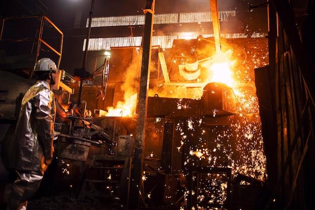 Operaio in tuta di protezione alluminata in piedi dalla fornace con ferro fuso caldo e scintille volanti, fonderia e produzione di acciaio industriale.