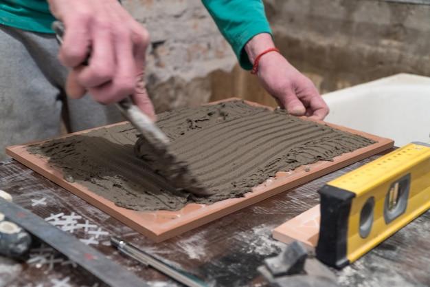Operaio applica adesivo cementizio sulle piastrelle. lavori di finitura, messa a fuoco sfocata. la tecnologia di posa delle piastrelle.