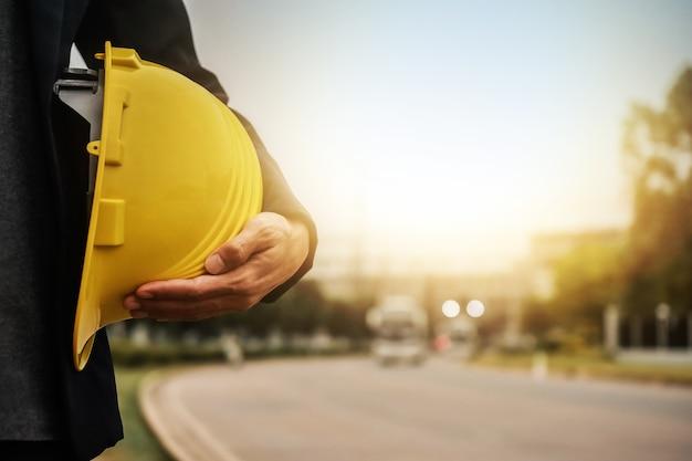L'ingegnere di architettura del lavoratore tiene la sicurezza del casco del casco per la costruzione